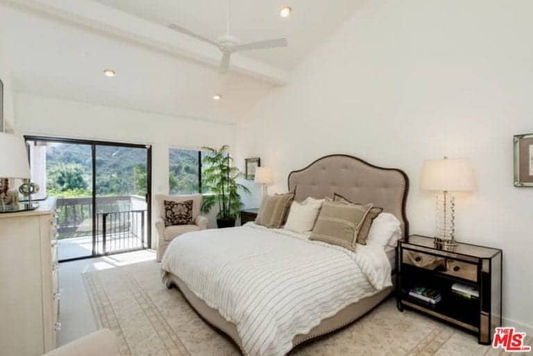 White bedroom features a king's bed on a wide rug featuring a couple of table lamps on both side. Glass door leads to private terrace area.