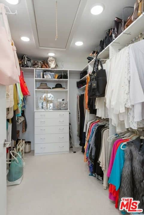 The female closet boasts multiple shelving and storage lighted by recessed ceiling lights.
