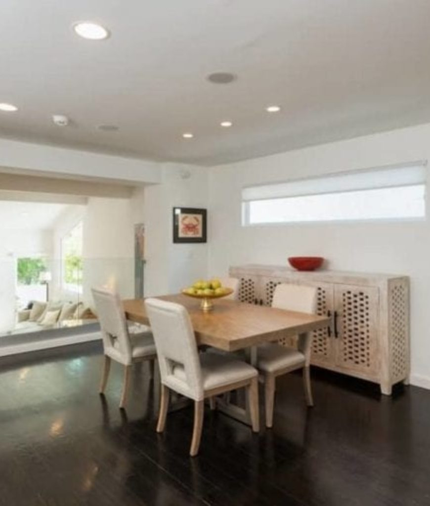The square dining set is surrounded by white walls and hardwood flooring lighted by recessed ceiling lights.
