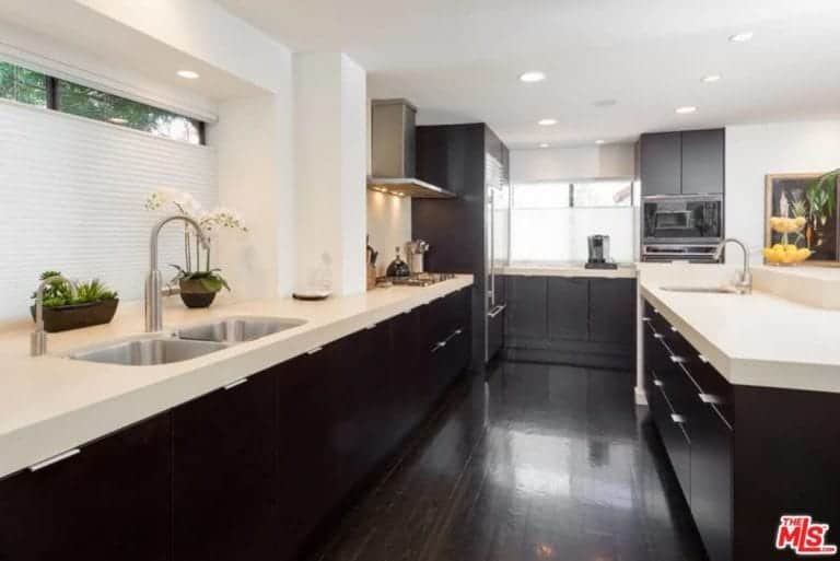 This kitchen boasts espresso finished counters and hardwood flooring along with smooth white countertops.