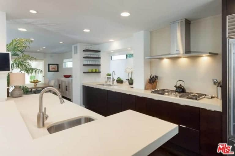 Another look of the kitchen showcasing the smooth white countertops along with white walls lighted by recessed ceiling lights.