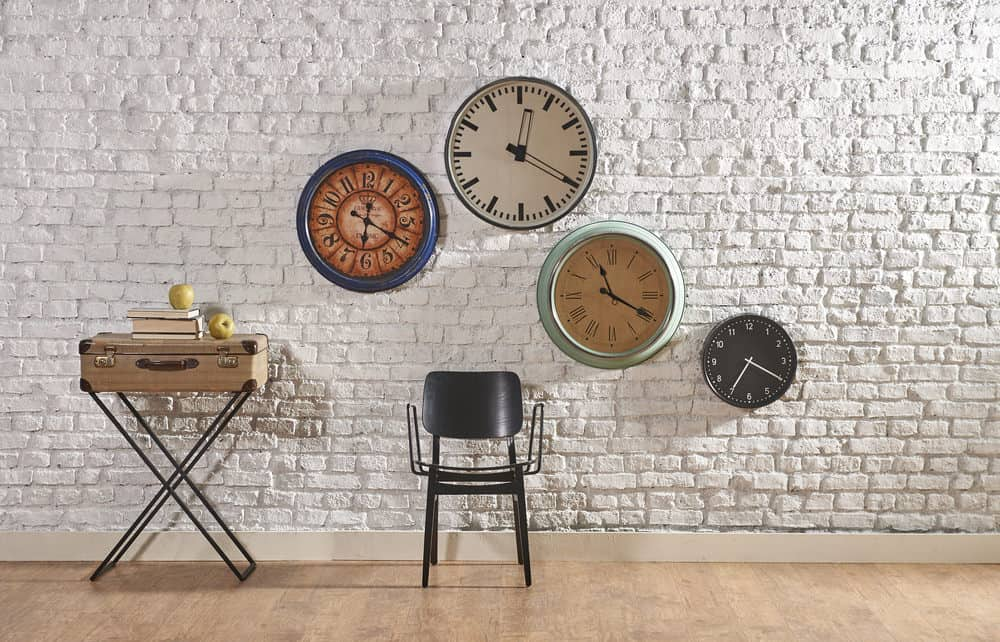 Wall with several wall clocks on it