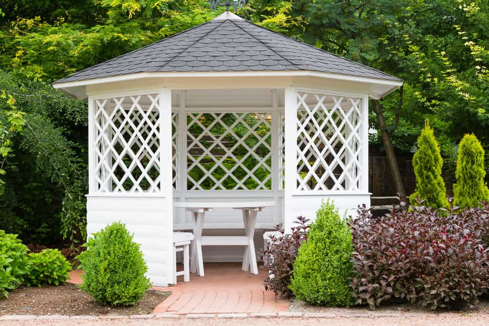 White wooden hexagon gazebo in the backyard