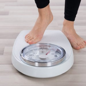 Women stepping onto scale to weigh herself