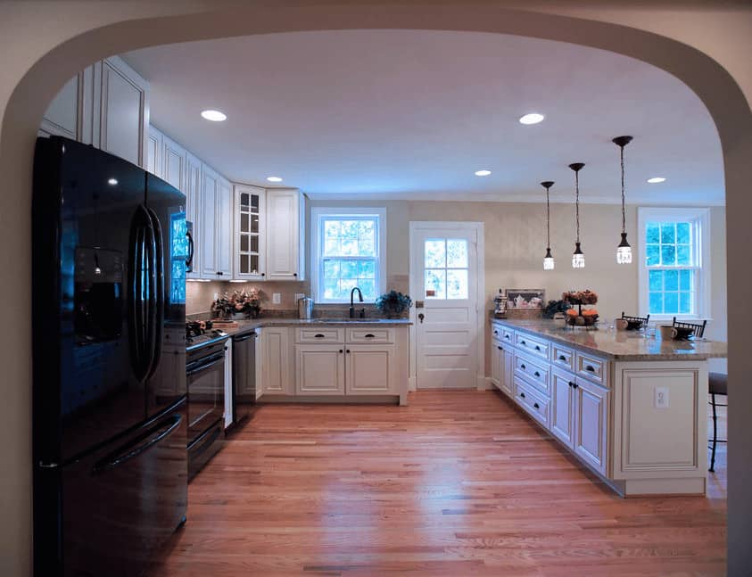 An arched doorway opens to this spacious kitchen with a wood plank flooring and white framed windows and door.