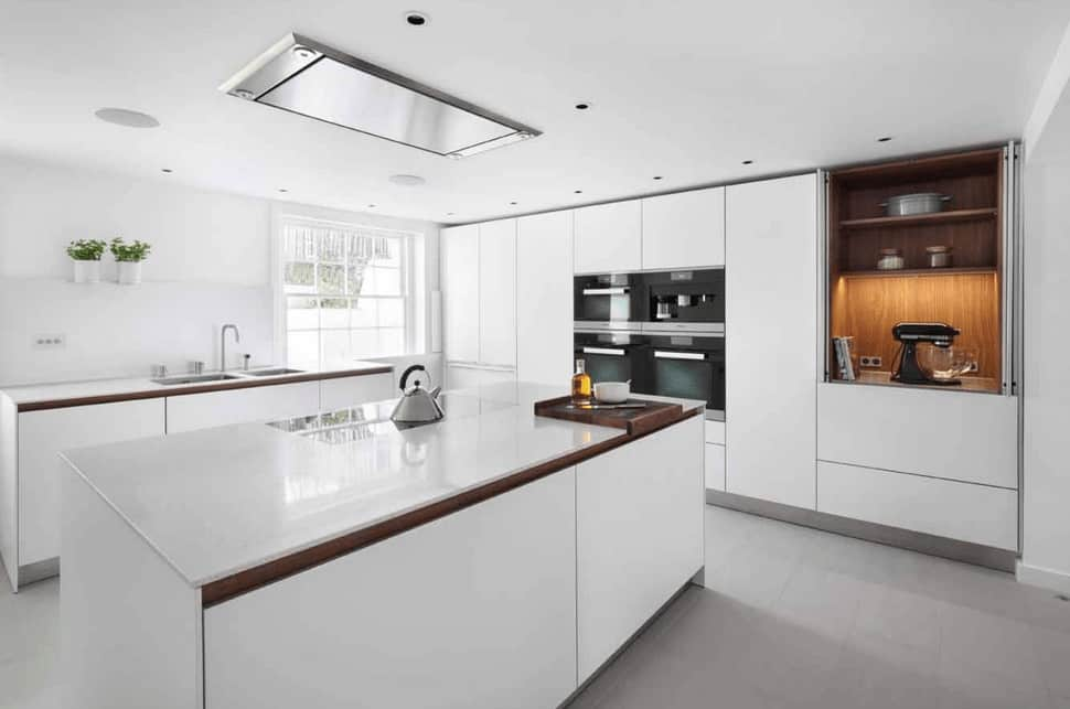 Clean white kitchen sporting a minimalist design. It has modern black appliances and sleek cabinetry with open shelving on the side.