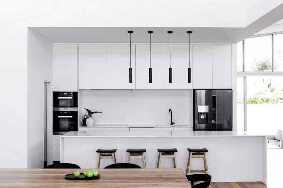Sleek kitchen showcases white cabinetry accented with black appliances and stools illuminated by black pendant lights that hung over the island bar.