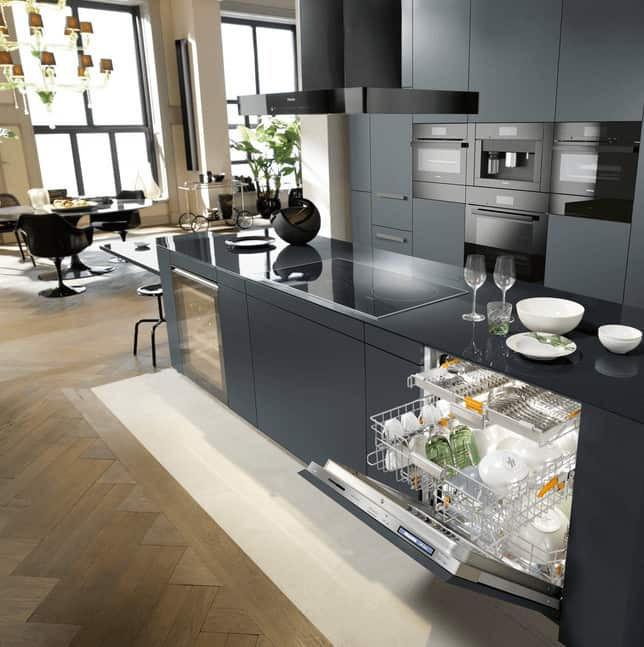 Contemporary kitchen features a gray breakfast island fitted with wine fridge, smart dishwasher and a cooktop paired with vent hood. It includes matching cabinetry fixed with black wall ovens.