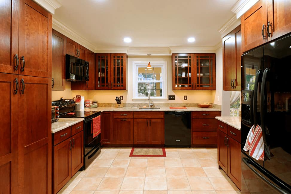 U-shaped kitchen features wooden cabinetry lined with white crown molding and fitted with glossy black appliances.