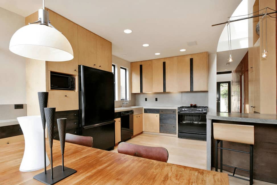 Modern kitchen showcases hardwood flooring that matches with light wooden cabinetry lined with black strips. It includes black appliances, metal drawers and a wooden dining set lighted by a white dome pendant.