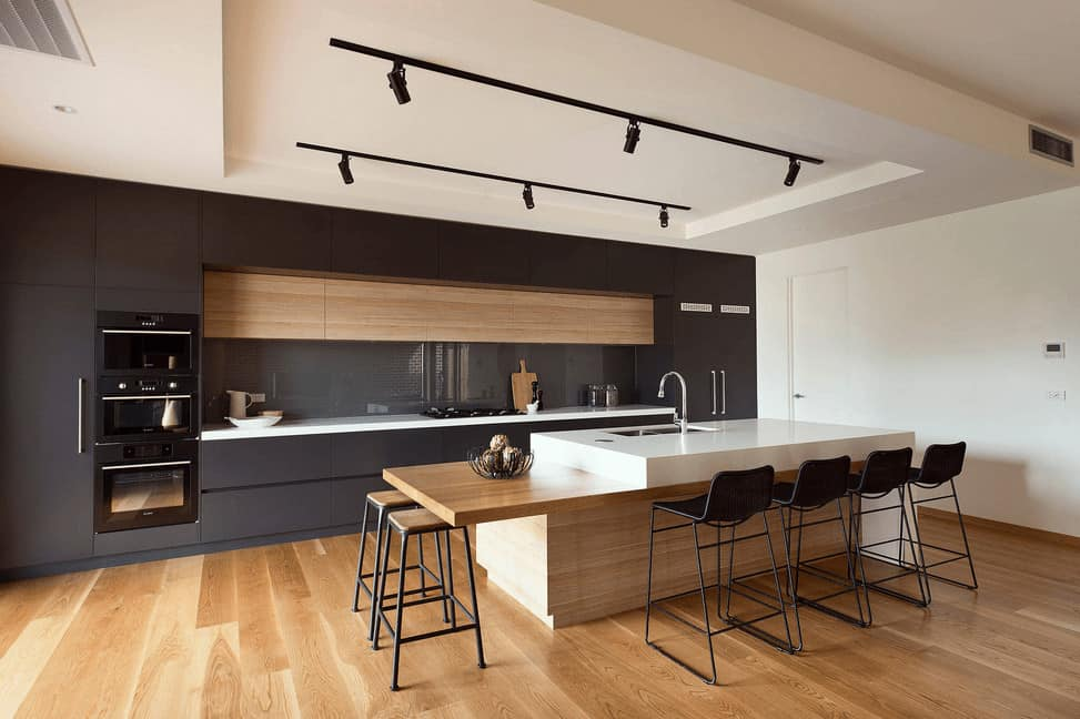 This kitchen offers a wooden breakfast island and sleek black cabinetry fitted with a black fridge and wall ovens. It has wood plank flooring and tray ceiling fixed with track lights.