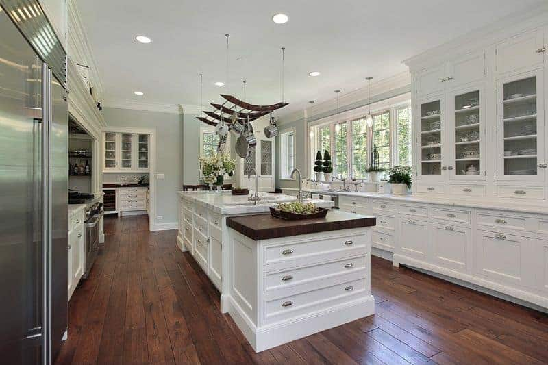 Another look of the white large Mediterranean kitchen featuring a hardwood flooring, white cabinetry and large center island with marble countertop.