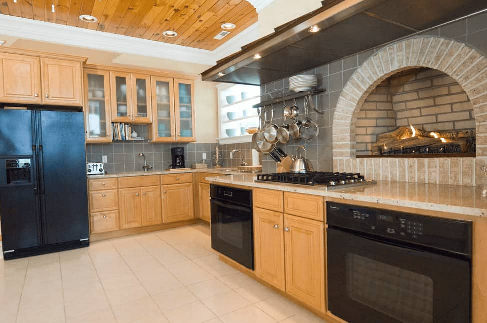 Cozy kitchen features an arched brick fireplace with wall mounted pot rack on the side fixed to the gray tile backsplash. It has natural wood cabinetry fitted with black appliances.