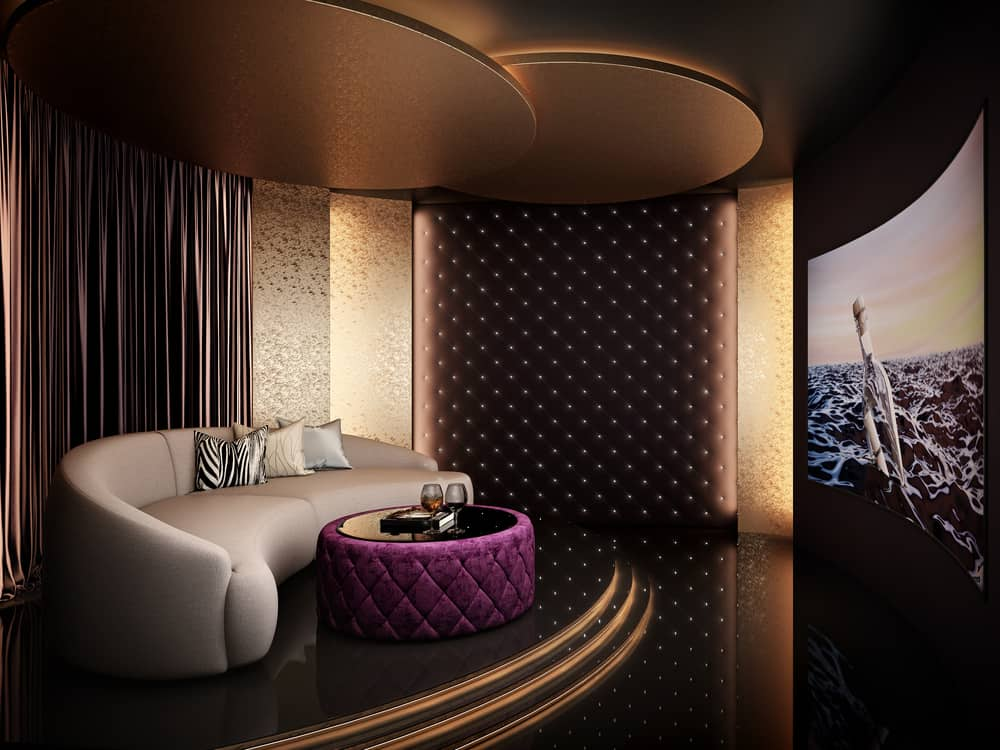 Elegant home theater with curved sofa, wall lighting and large curved viewing screen.