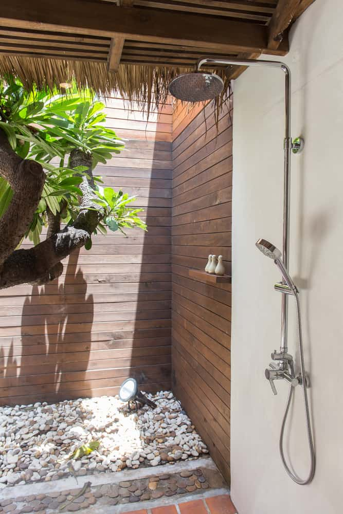 A modern and traditional combo outdoor shower featuring wooden walls providing privacy.