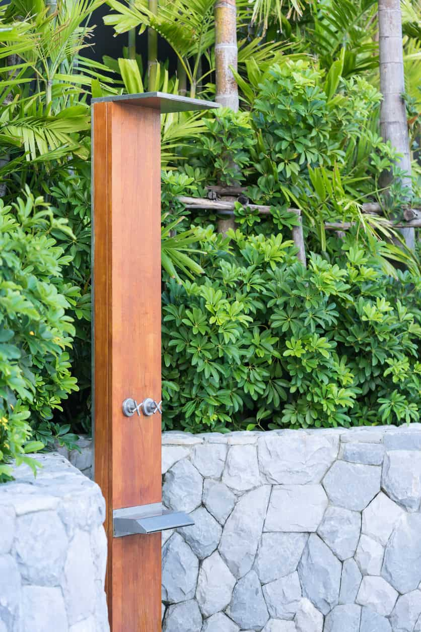 A modish outdoor shower surrounded by gorgeous greenery.