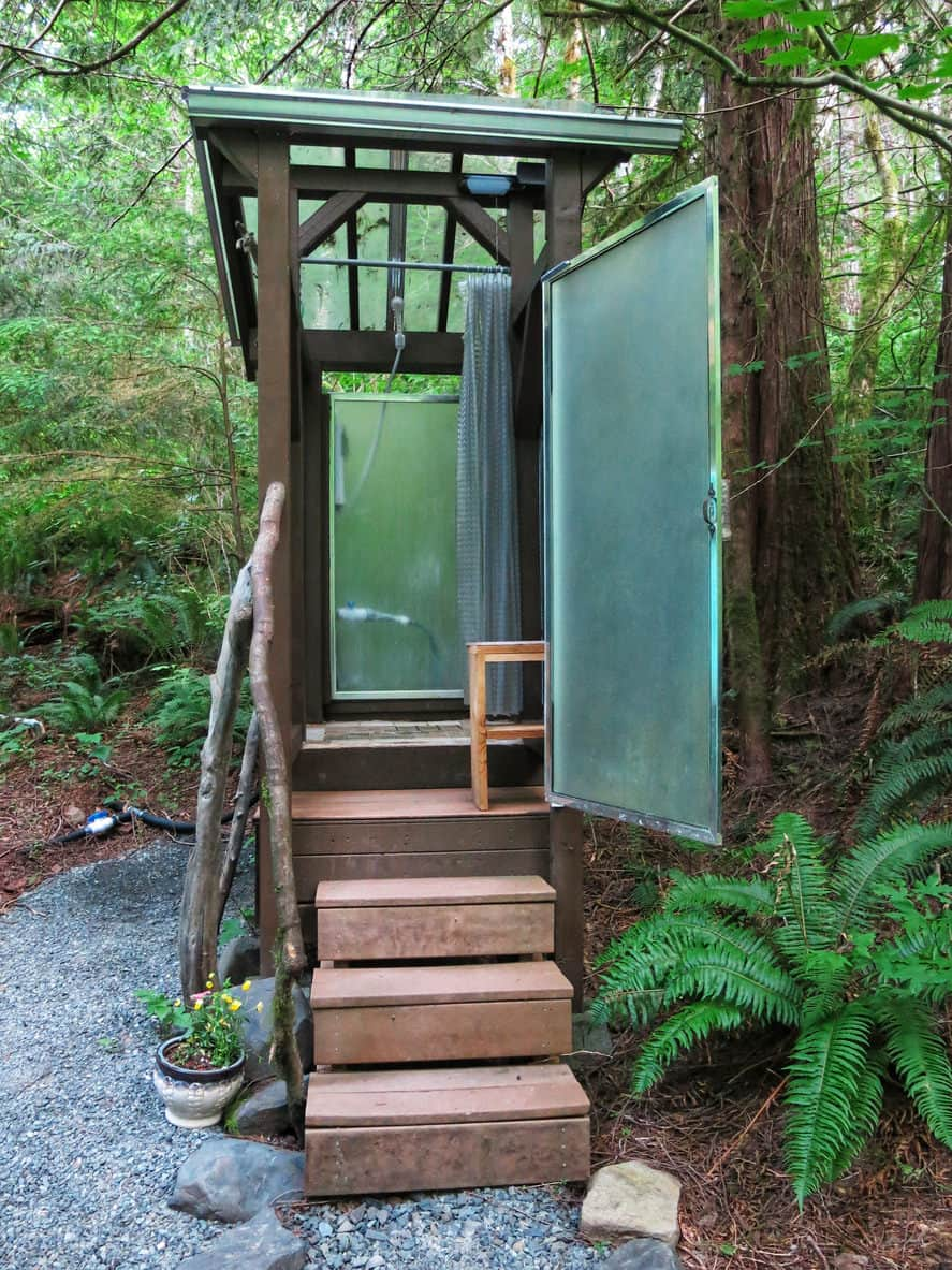 A walk-in outdoor shower with a very stylish built set on the forest-like outdoor area.