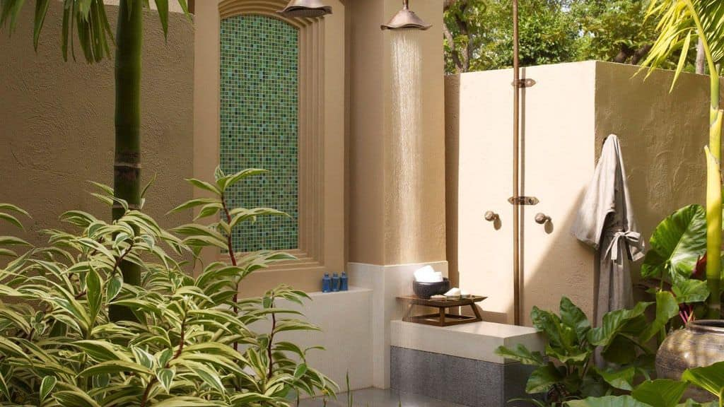 The lovely plants surround this outdoor shower. The shower head is set high.