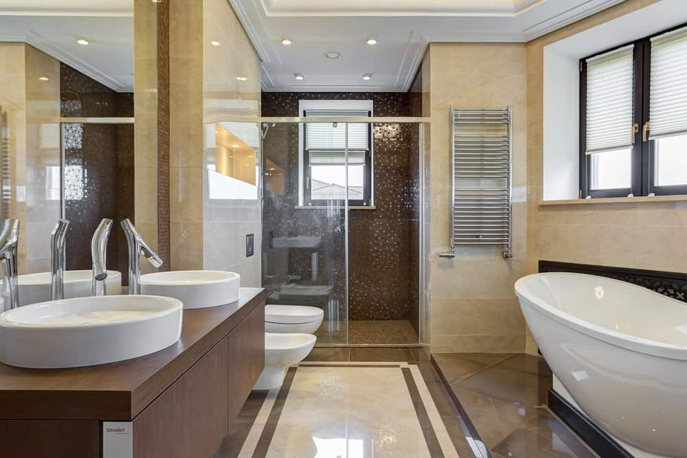 Contemporary beige and dark brown bathroom with two sinks and freestanding tub.