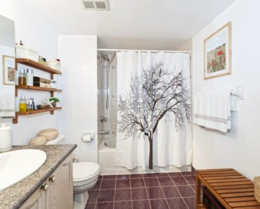 Bathroom with shower curtain with tree mural
