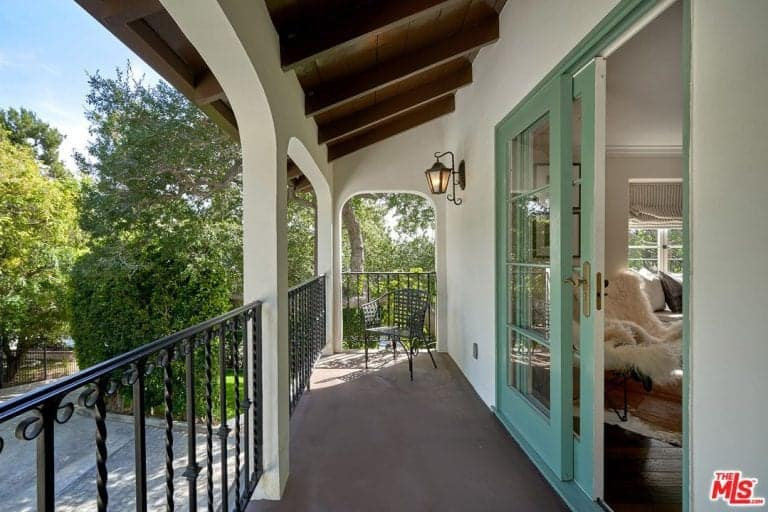 The primary bedroom leads to a private balcony overlooking the house's frontyard.