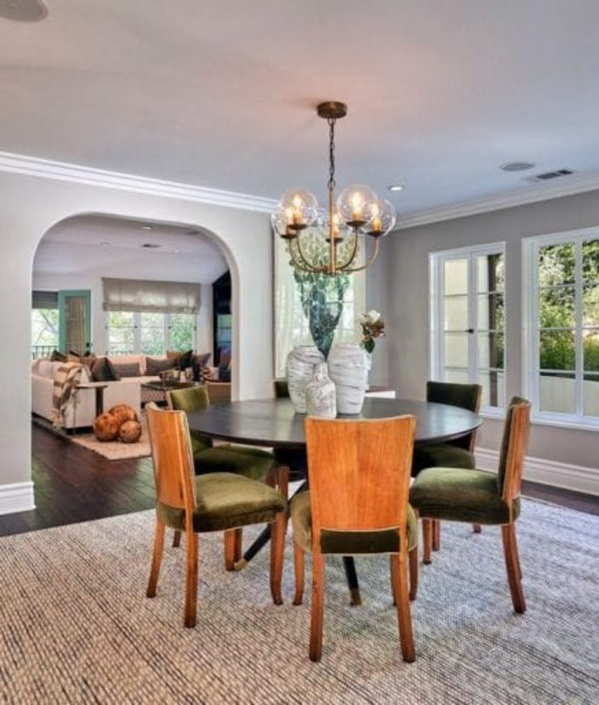 The dining room looks elegant with its table lamps and small chandelier. The round table looks perfect with the chairs.