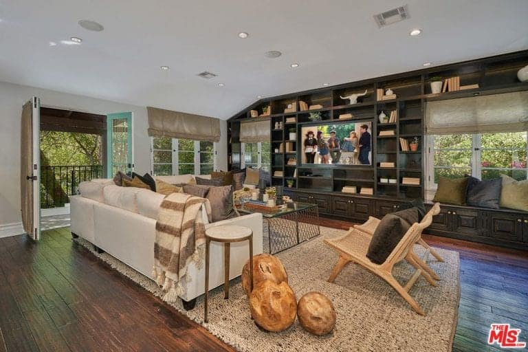 This living room boasts a dark wood built-in shelving that extends as seat nooks accented with multi-colored pillows. It has a perforated coffee table paired with wooden chairs and white sectional sofa.