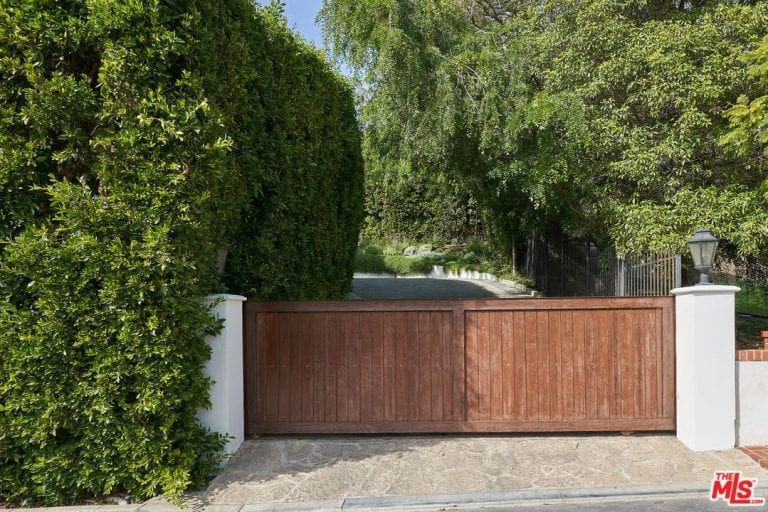 A wide wooden gate covers the entrance to the property while healthy greens surrounds the area.