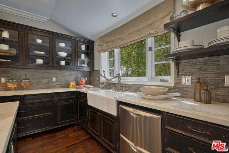 Another look of the kitchen boasting its smooth marble countertop with multiple shelving and cabinets