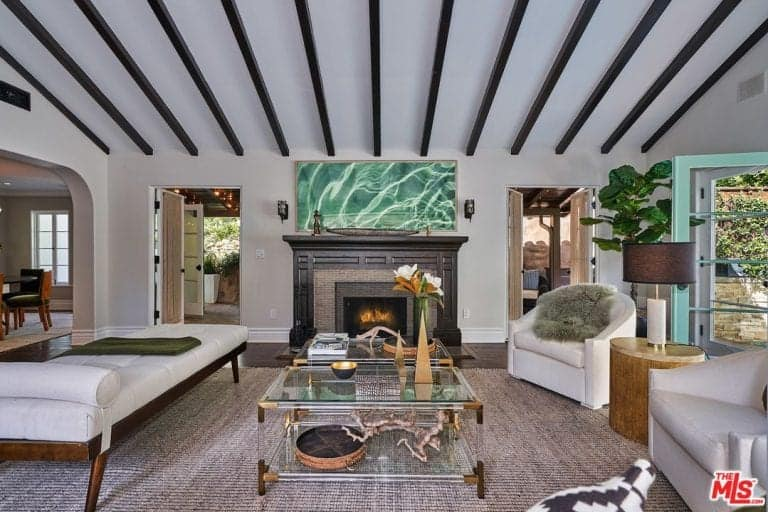 The formal living room boast elegant lounging spaces with a fireplace together with a stylish rug and vaulted ceiling.