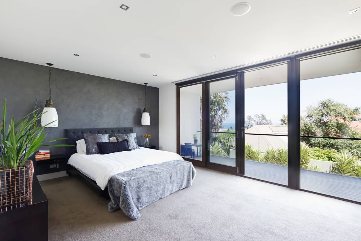 Primary bedroom with floor-to-ceiling windows leading to balcony and plants on the dresser.