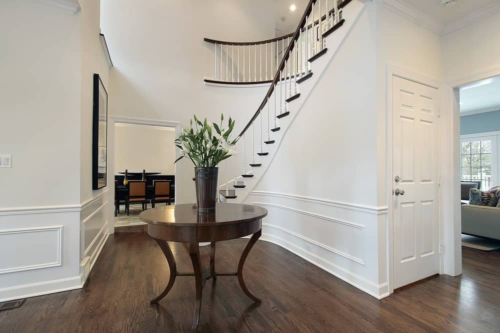 Nice foyer with dark wood flooring, winding white stairs and round center table.
