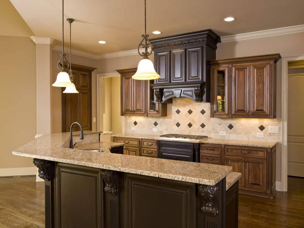 Bright kitchen with white walls and brown cabinetry and flooring. The curved center island is lighted by three pendant lights.