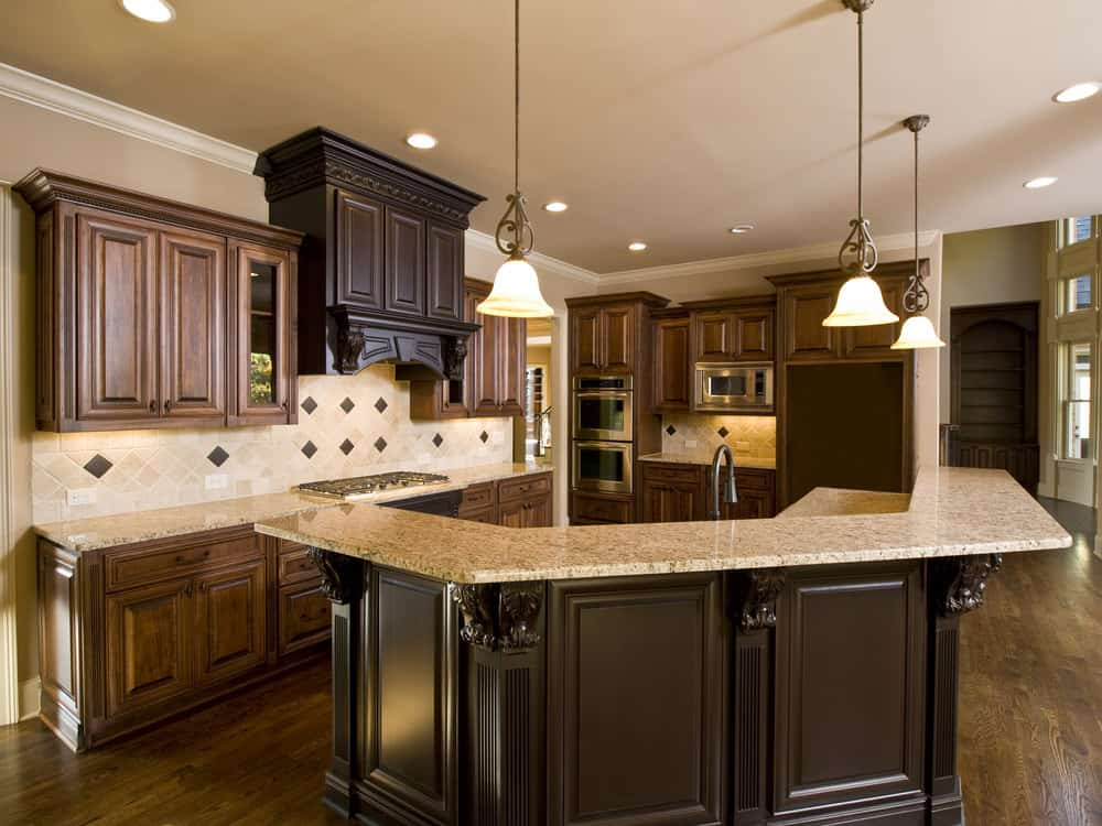 Bright kitchen filled with brown cabinetry and flooring. The marble countertops blends well with the classy ceiling lights. The curved center island is long.