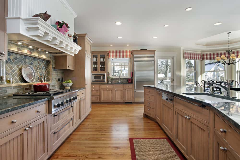 Bright kitchen with brown cabinetry and hardwood flooring. The scattered recessed ceiling lights brighten the space. The curved center island features a granite countertop.
