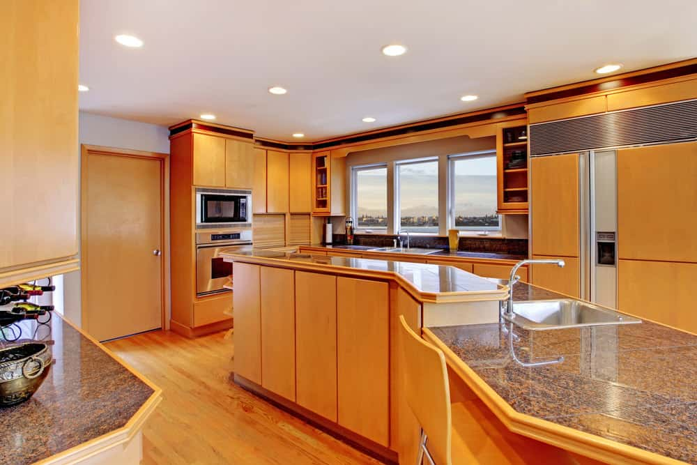 This kitchen is surrounded by walnut finished cabinetry and vinyl flooring. The narrow center island features a granite countertop.