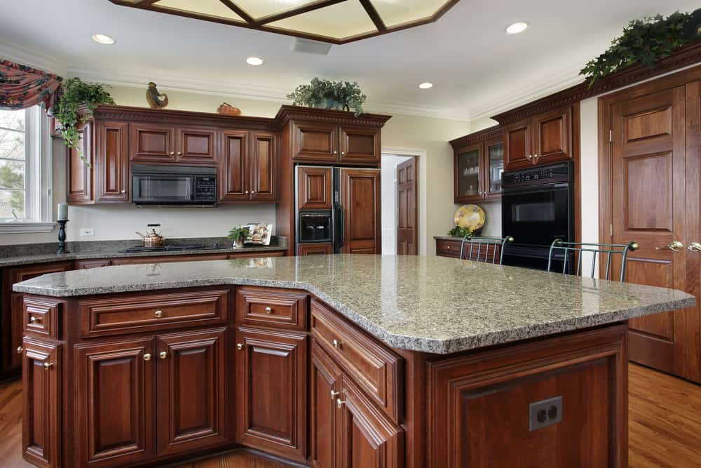 Kitchen with white walls and brown cabinetry. The ceiling looks glamorous along with its recessed ceiling lights. The curved center island features a granite countertop.