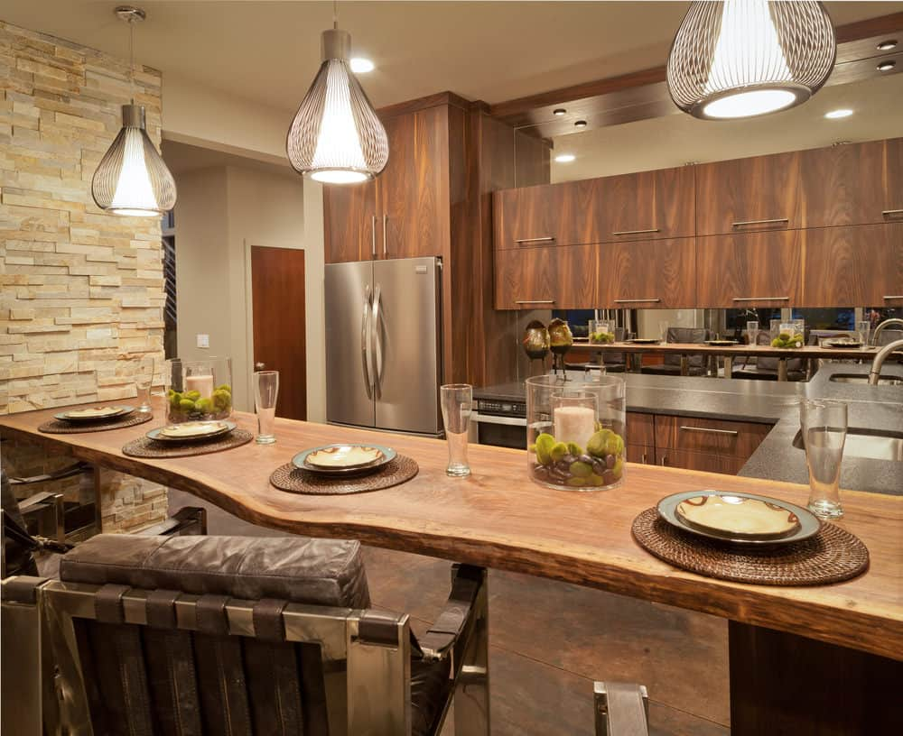 Rustic eat-in-kitchen with wood flat panel cabinets, stone tile flooring, and a trio of teardrop pendant lighting over a wood surface peninsula.