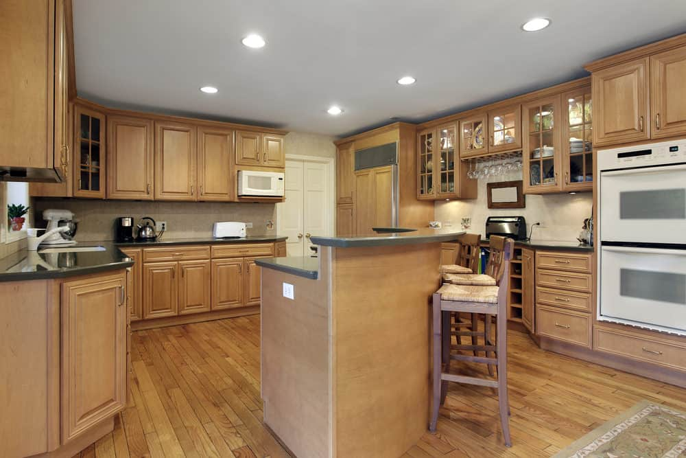 A kitchen surrounded by brown colors, cabinetry to flooring. The counters are made of granite. The curved center island features a space for a breakfast bar.