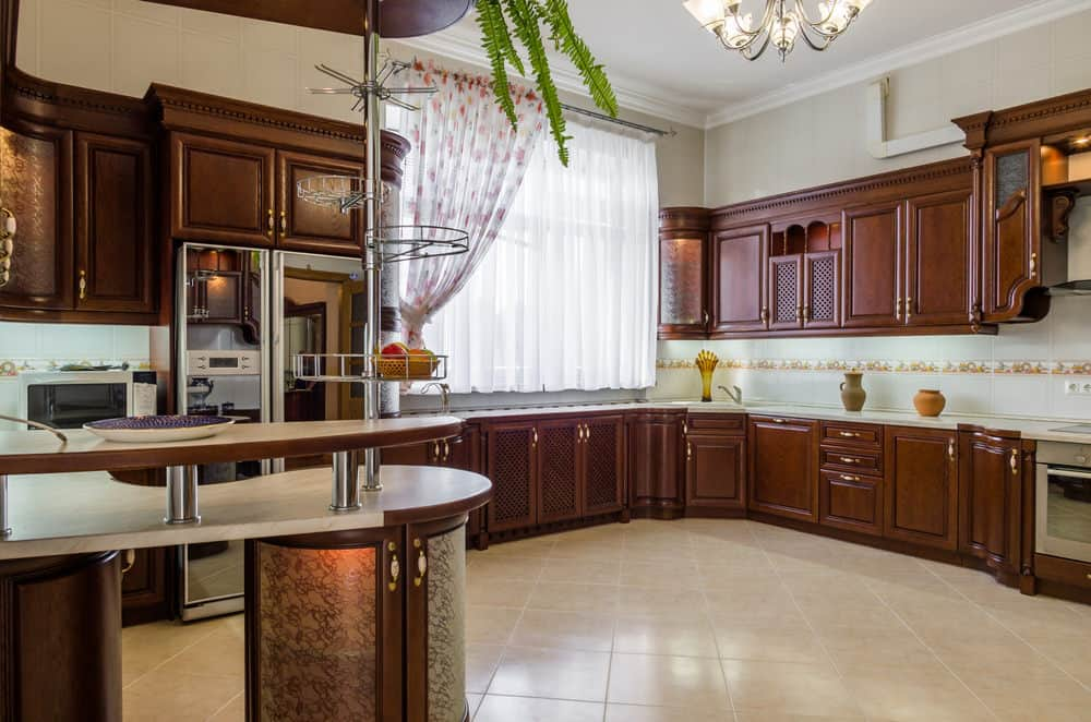 Large kitchen with white walls and rustic cabinetry with tiles flooring. The kitchen also boasts a curved center island.
