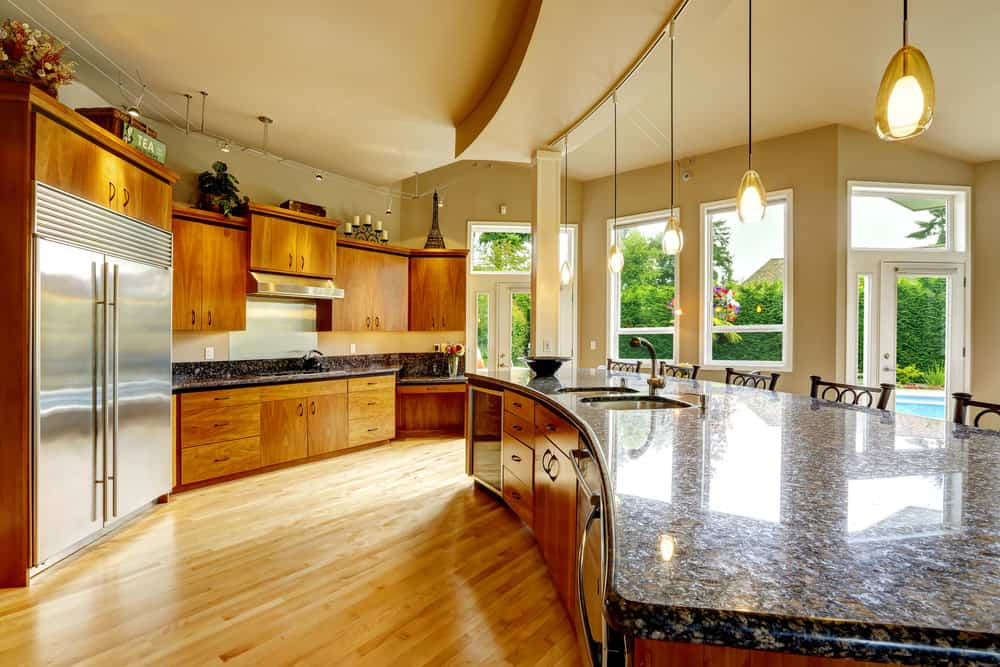 A large kitchen with a rustic details to it boasts a large kitchen island with a granite countertop lighted by four beautiful pendant lights.