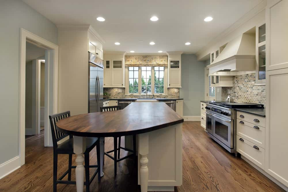 Kitchen with pale blue walls, white cabinetry and trims, wood flooring, and an L-shaped kitchen island with wood surface and seating.