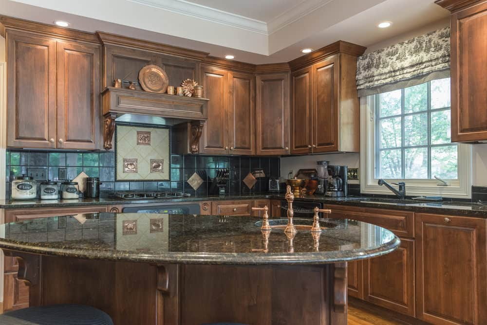 This Kitchen Is Filled With Brown Cabinetry The Counters Boast Granite Countertops Center