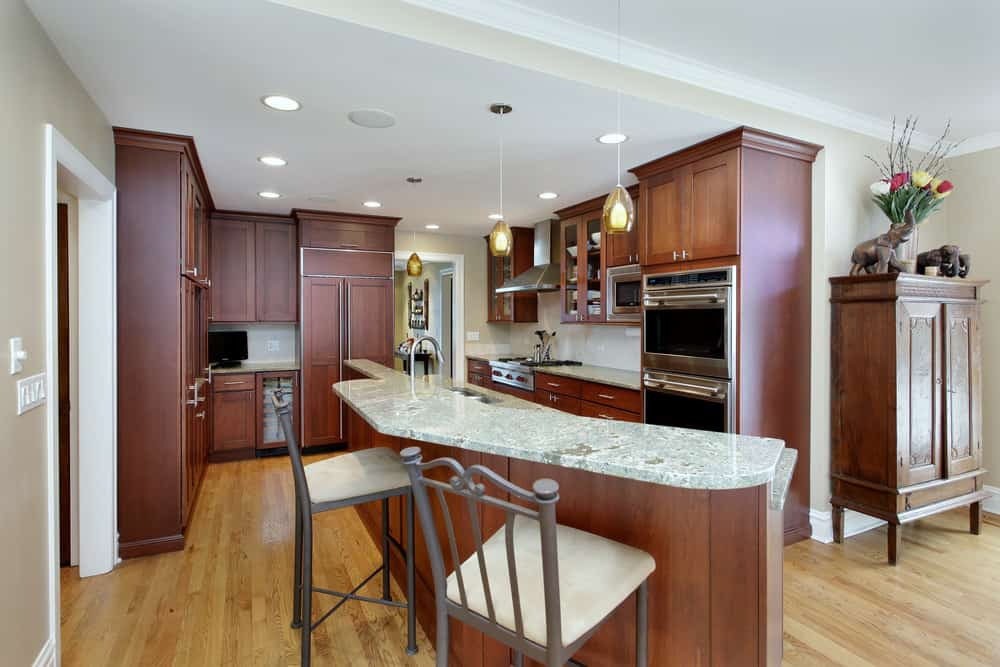 This kitchen feature a brown cabinetry and a narrow kitchen island with a marble countertop lighted by pendant and recessed lights.