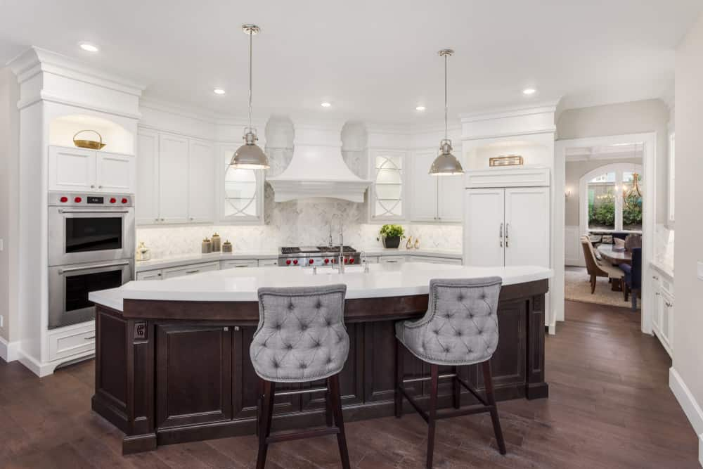 White Kitchen With A Hardwood Flooring The Curved Center Island Boasts Very Smooth And