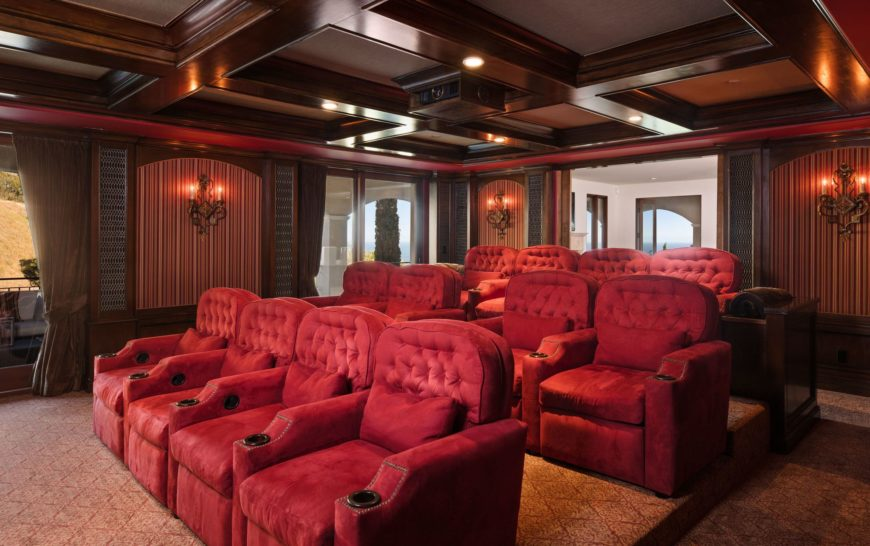Large home theater with stylish red seats and classy carpet flooring lighted by stunning wall lights.