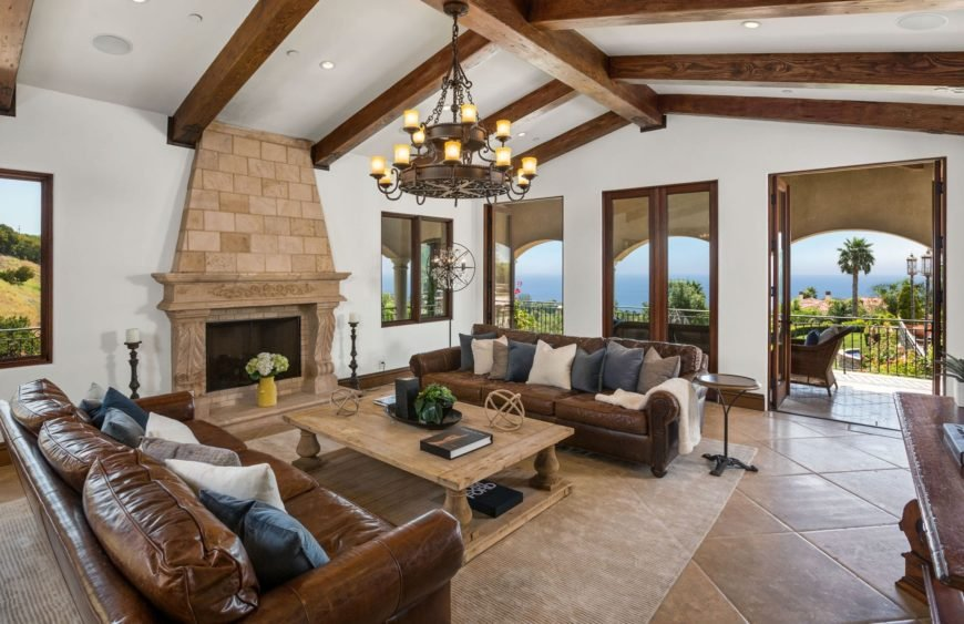 Mediterranean living room featuring brown leather seats and a classy fireplace, along with a doorway leading to the home's balcony.