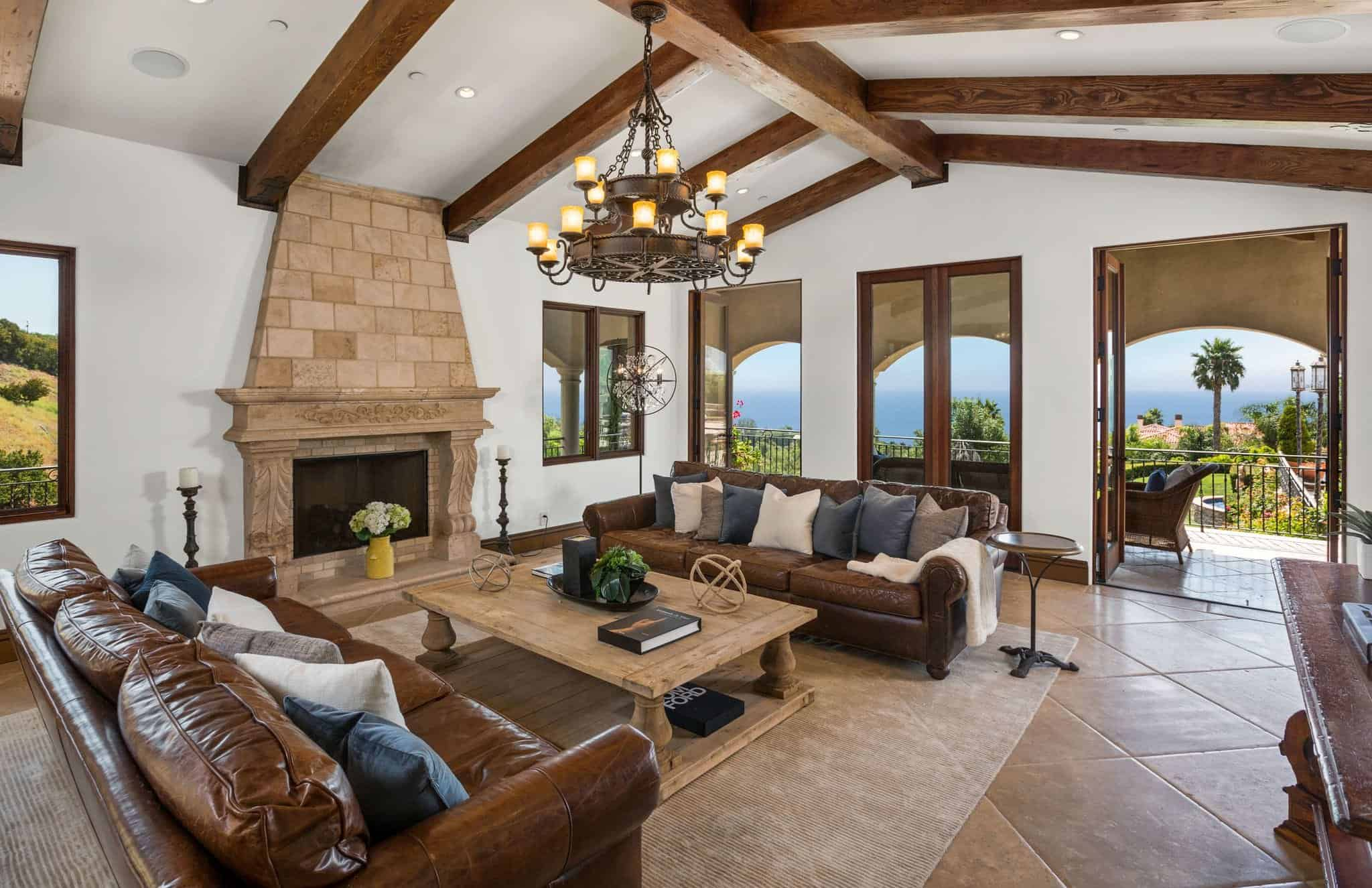 A Mediterranean living room with vaulted ceiling with beams and a set of brown leather couches near the fireplace lighted by a classy chandelier.