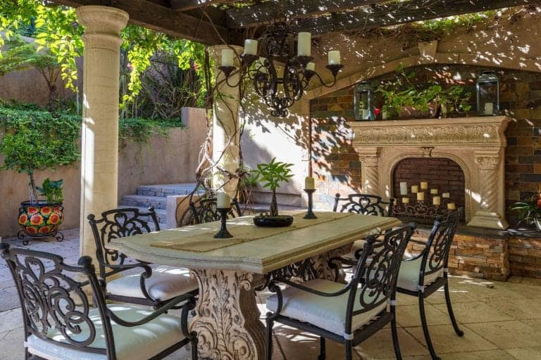 There's also an outdoor dining area with a fireplace and a chandelier.