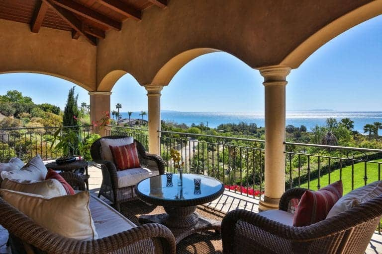 Luxurious patio featuring classy seats and center table overlooking the beautiful wide garden and sea.
